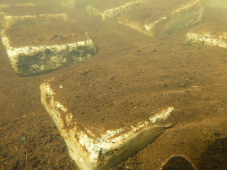 A stone covered in sediment in an experimental channel.  Image: Aarhus University